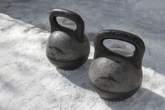 Two old black heavy kettlebell stand on the snow. stock photos