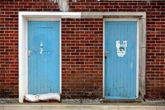 Two Old Blue Doors Surround by Brickwork. Two old blue wooden doors set into red brick wall in seaside town of Weymouth Royalty Free Stock Image