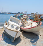 Two old boat on the shore. Two old boat lying on the shore of the port, leaning against each other Royalty Free Stock Images