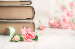 Two old books on wooden table among pretty little pink roses, te Stock Images
