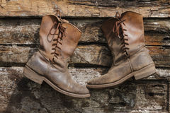 Two old boots hanging on a wooden wall Stock Photos