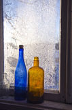 Two old bottle on frosty farm winter window Royalty Free Stock Images