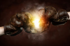 Two old boxing gloves with Skulls hit together. Two old brown boxing gloves with Skulls hit together stock images