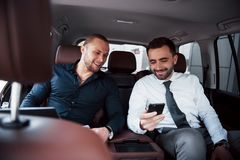 The two old business friends conclude a new agreement in an informal setting in the car`s interior.  royalty free stock image