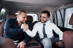 The two old business friends conclude a new agreement in an informal setting in the car`s interior.  stock image