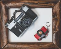 Two old camera lie in wooden frame on a white background royalty free stock photo