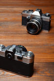 Two old cameras on wooden background. Stock Image