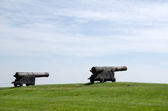 Two old canons. On a hill with green grass Royalty Free Stock Photography