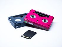 Two old cassettes of red and black colors with white background and current sd card. Two old video cassettes one of pink and the other black, photo light box Royalty Free Stock Images