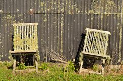 Two old chairs. A couple of old chairs left behind a barn stock photography