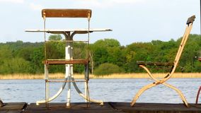 Two old chairs and one table on jetty. Two old metal chairs and a table placed on a wooden jetty at a river or lake. Forest and nature in the background stock video
