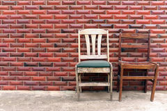 Two old chairs by a red brick wall Stock Photography