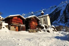 Two old chalets and a chapel in the snow Stock Photo