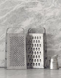 Two old cheese graters on a kitchen counter Stock Photos