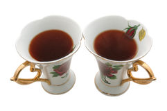Two old china teacups. Two old china teacups with strong tea for two stock photography
