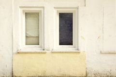 Two Old Closed Windows  in the Old White Concrete Wall Royalty Free Stock Images