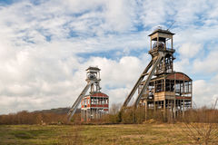 Two old coal mines. Two old coal mine towers against cloudy sky stock photography