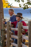 Two Old Cowboys Standing by Rail Fence royalty free stock photography