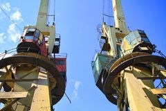 Two old cranes in the dockyard. Two old, rusty, yellow cranes in the dockyard - close-up Royalty Free Stock Photo