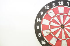 Two old darts on an old dart board with many holes Stock Image
