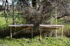 Two old desks near a fence on a garden. Royalty Free Stock Photography