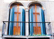 Two old door-windows with a slightly crooked balcony stock images