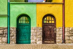 Two old doors on different buildings. Two old doors on different colorful buildings. Which way royalty free stock photos