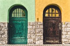 Two old doors on different buildings. Two old doors on different colorful buildings. Which way royalty free stock photography