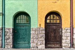 Two old doors on different buildings. Two old doors on different colorful buildings. Which way royalty free stock image