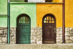 Two old doors on different buildings. Two old doors on different colorful buildings. Which way stock photography