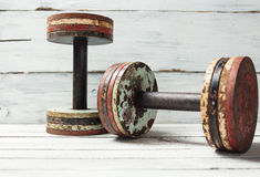 Two old dumbbells on white wood Stock Photo