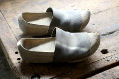 Two old Dutch style wooden clogs in the workshop of a shoemaker Stock Photos