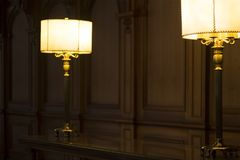 Two old fashioned lamps on a desk in a wood paneled room royalty free stock image