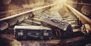 Two old fashioned a suitcases on railroad tracks. Two old fashioned forgotten a suitcases lie on railroad tracks Stock Photo