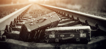 Two old fashioned a suitcases on railroad tracks Stock Images