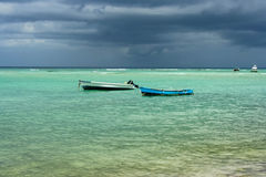 Two old fishing boats in clear sea with a stormy background Stock Photo