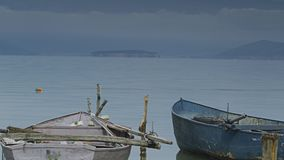Two old fishing boats sitting on the bay. A video of some old fishing boats sitting on the bay of a lake stock footage
