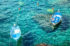 Two old fishing boats in the turquoise waters. Of the Mediterranean Royalty Free Stock Photo