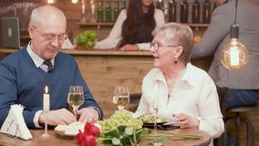Two old friends in their sixties catching up on what they`ve been up to lately over dinner in a restaurant royalty free stock photography
