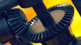 Two old gears rotating in mechanism. Two old gears slowly rotating in undefinied iron mechanism. Black parts on the yellow background stock video footage