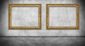 Two old golden frames. On gray wall Royalty Free Stock Photos