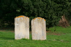 Two old gravestones close together. Two very old gravestones stand together. The inscriptions have been worn by time and have now faded Royalty Free Stock Photography