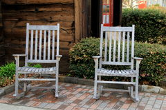 Two old gray Adirondack chairs on brick Royalty Free Stock Photography