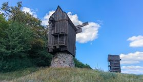 Two old historic wooden windmills on a hill top Stock Photos