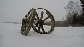Two old historical horse carriage wheels on  field and winter snowfall, time lapse 4K stock footage