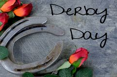 Two old horse shoes paired with silk red roses on a scratched up steel background stock image