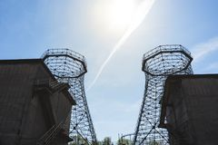Two old industrial cooling towers. Framed of industrial buildings with sun on blue sky stock image