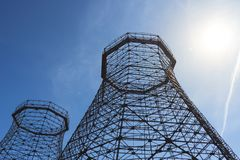 Two old industrial cooling towers. With sun on blue sky stock image