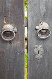 Two old iron ring handles on a door standing ajar Stock Photos