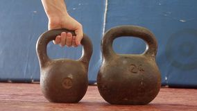 Two old kettle bell. Iron kettlebell in the man`s hand on a blue wooden background old shabby. Iron kettlebell in the man`s hand on a blue wooden background old stock video footage
